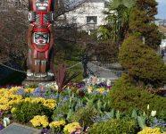 Totempfahl und Blumen in Victoria, BC